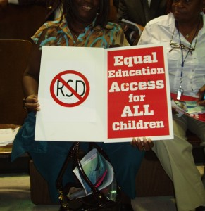 Local resident holds anti-RSD sign at 2010 public hearing. ©2010 Kristen Buras.